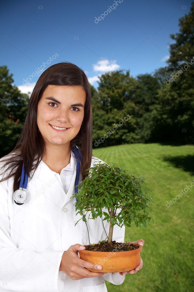 Smiley female doctor with a tree outdoors — Stock Photo #7710725