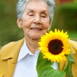 Senior woman with a sunflower — Stock Photo