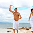 Couple running with sarong — Foto de Stock