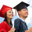 Couple of graduates outdoors — Stock Photo #7732353