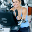 Woman at the gym cycling — Stock Photo