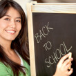 Woman writing on a chalkboard - Stock Photo
