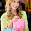 Stock Photo: Womwith bags and piggybank