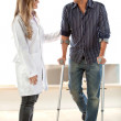 Patient in crutches - Stock Photo
