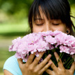 Woman smelling flowers - Stock Photo