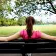 Stock Photo: Woman sitting on a bench
