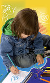 Boy colouring on a notebook — Stock Photo