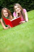 Girls reading a book outdoors — Stock Photo