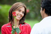 Woman getting a red rose — Stock Photo
