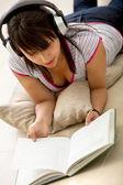 Kobieta czytanie i słuchanie muzyki — Zdjęcie stockowe