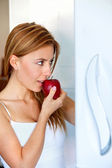 Woman at the fridge with an apple — Стоковое фото
