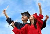 Couple of graduates outdoors — Stock Photo