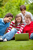 Friends with laptop outdoors — Stock Photo