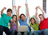 Excited friends with a laptop — Stock Photo