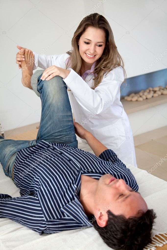 Physiotherapist doing therapy to a man on his leg — Stock Photo #7731999