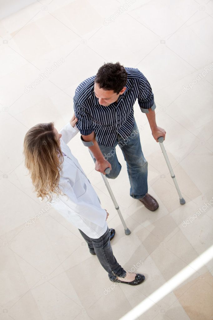 Doctor and a man with crutches in a hospital — Stock Photo #7732153