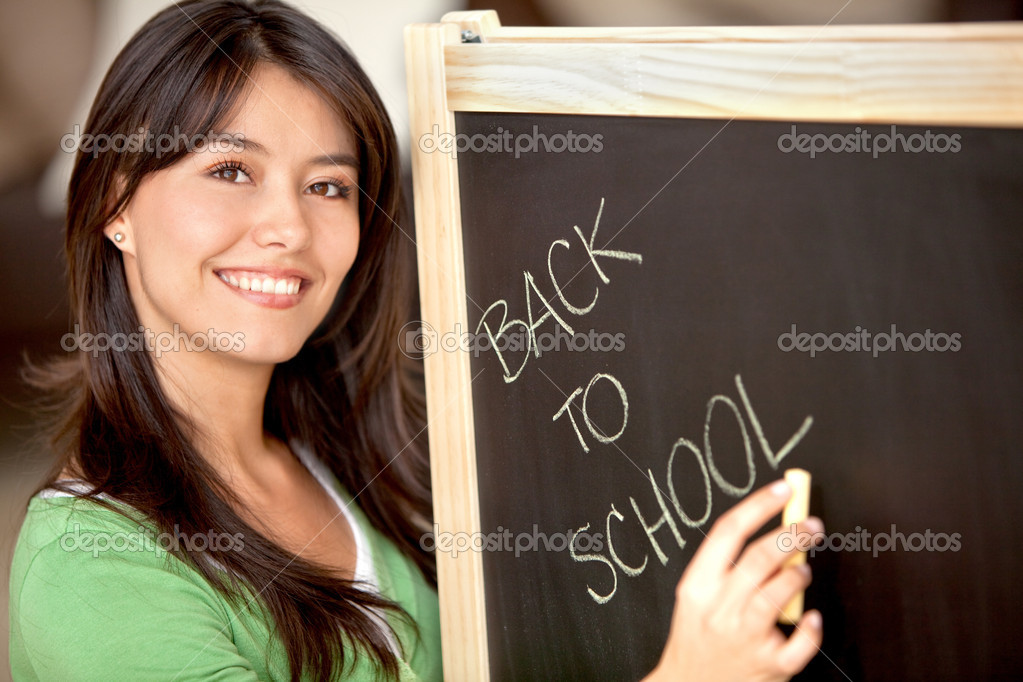 Woman writing 'back to school' on a chalkboard — Stock Photo #7732599
