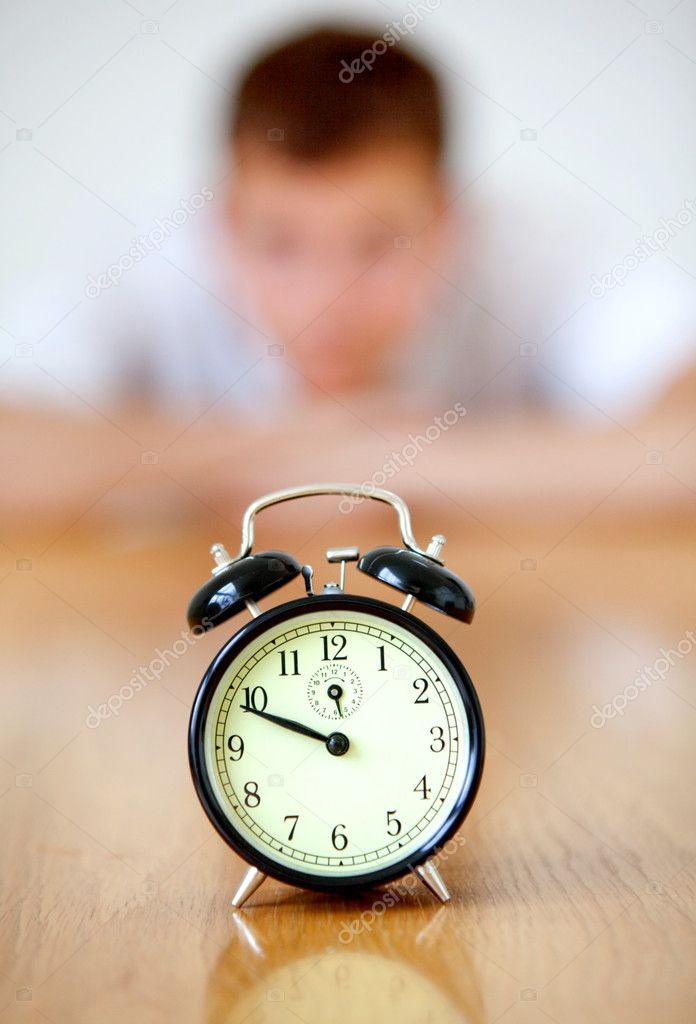 Man staring at an alarm clock isolated  Stock Photo #7736859