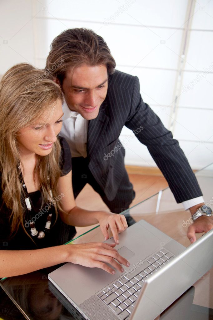Business couple working on a laptop in an office — Stock Photo #7738981