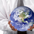 Business woman holding earth — Stockfoto