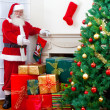 Santa with gifts and the tree — Stock Photo
