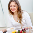 Woman eating her breakfast - Stock Photo