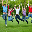 Friends jumping outdoors - Stock Photo