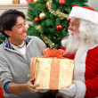 Santa giving a present to a man — Stock Photo