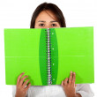 Woman covering with a notebook — Stockfoto