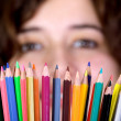 Girl with color pencils in front of her — Stock Photo