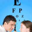 Eye test chart with doctor and patient - Stock Photo