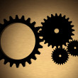 Stock Photo: Cogwheels over gold metal texture
