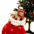 Christmas tree with sack full of gifts - Stock Photo