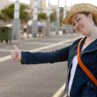 Girl hitchhiking on the street - Stock Photo