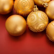 Gold christmas baubles on red — Photo