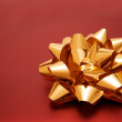 Beautiful golden ribbon on red gift — Stock Photo