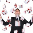 Business man with gifts falling down - Stock Photo
