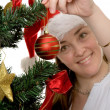 Girl decorating a christmas tree - Stockfoto