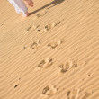 Girl waking on the beach - footprints - Stock Photo