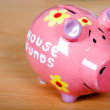 Piggy bank on a wooden surface - Stock Photo