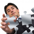 Business man arranging puzzle on white - Stockfoto