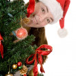 Santa behind a christmas tree — Stockfoto