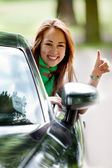 Woman in a car with thumbs up — Стоковое фото