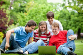 Friends outdoors with laptop — Stock Photo