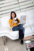 Woman with coffee and the newspaper — Stock Photo