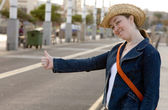 Girl hitchhiking on the street — Stock Photo