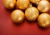 Gold christmas baubles on red — Stock Photo