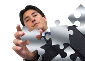 Business man arranging puzzle on white — Stock Photo