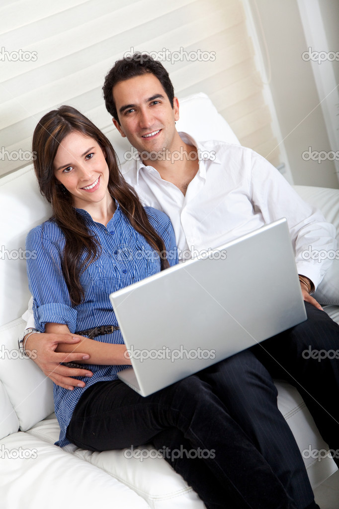 Couple portrait sitting on the sofa with a laptop computer — Stock Photo #7740189