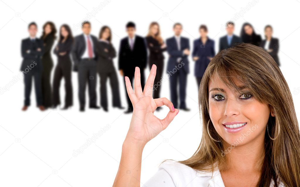 Businesswoman doing the ok sign with her team behind isolated on white — Stock Photo #7740365